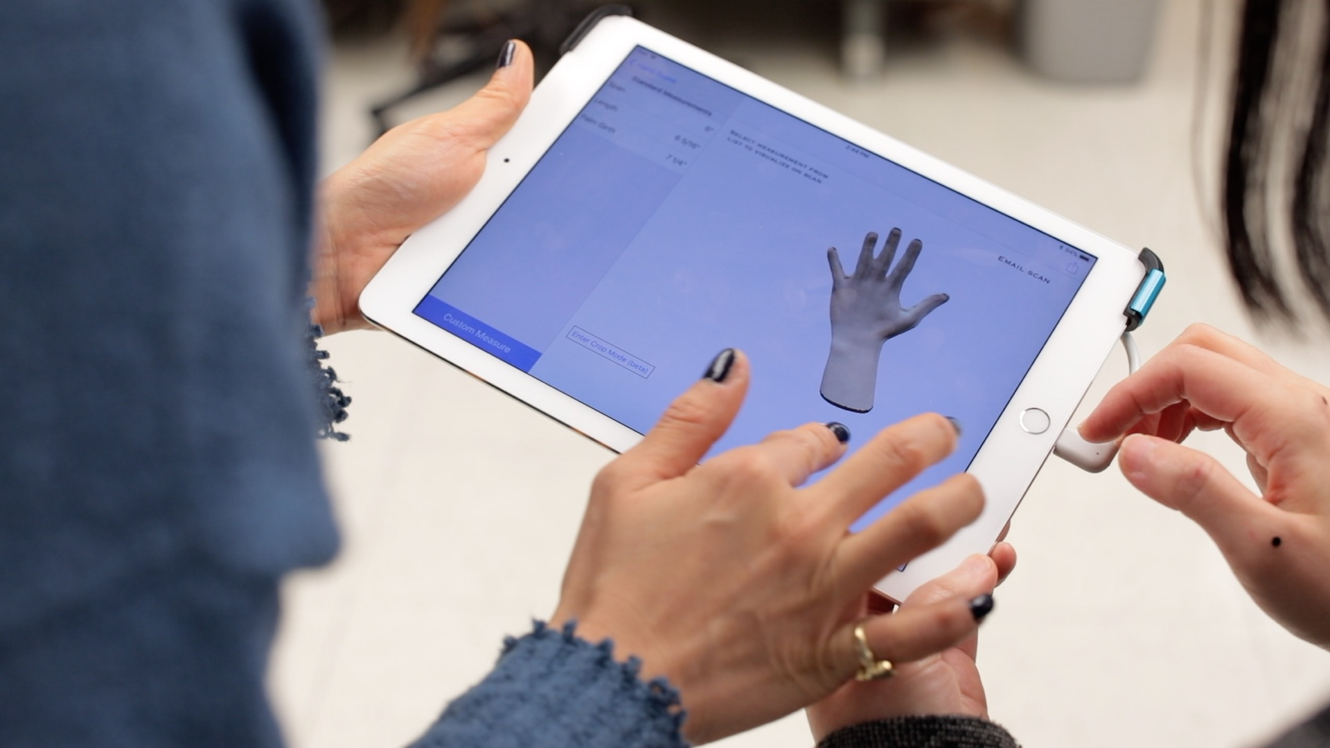 Close up of hands holding an iPad displaying research