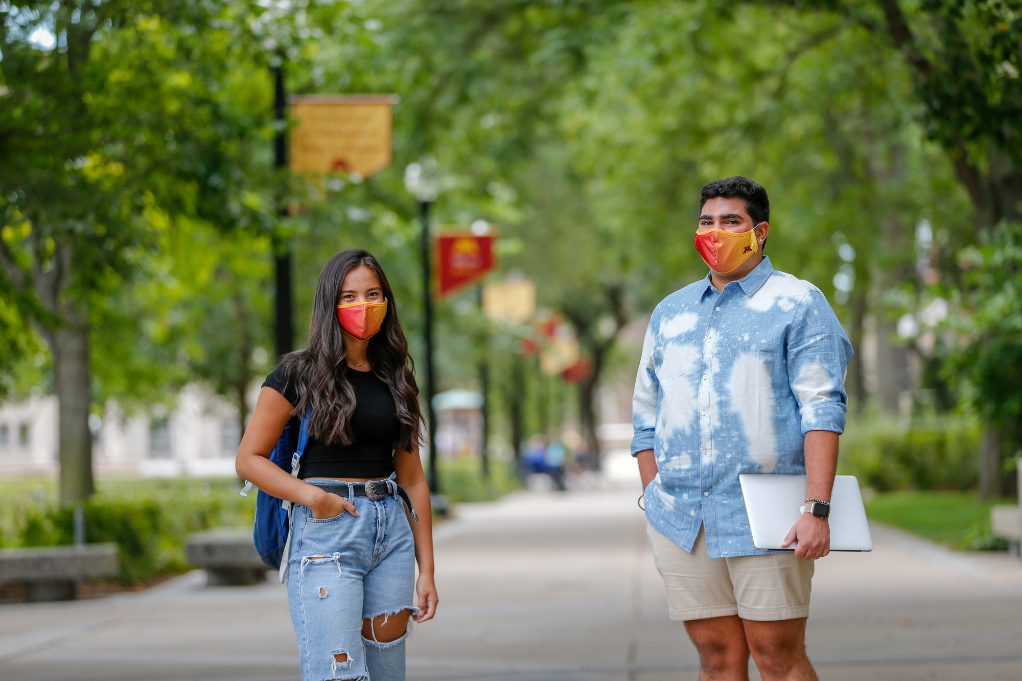 Two students walking on campus together wearing masks